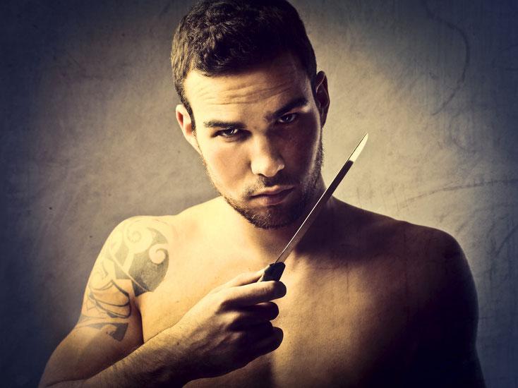 junger Mann mit freiem Oberkörper und Messer in der Hand; Privatdetektiv Dortmund