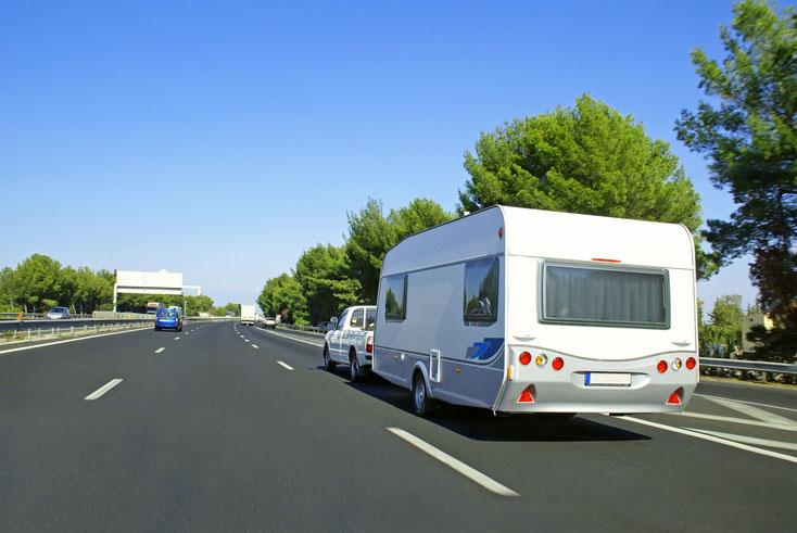 Caravan mit Zugfahrzeug auf einer Autobahn. Detektive der Kurtz Detektei Berlin