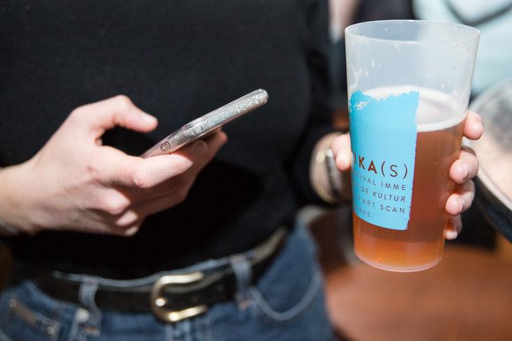 Photo d'un verre de bière à l'effigie du Festival Immersif de Kultur et d'Art Scandinave et Nordique FIKAS tenue par une jeune femme avec son téléphone intelligent par Marie Deschene photographe pour Pakolla