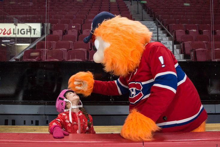 Youppi la mascotte des Canadiens tapote la tête de la fille d'une employée de Tourisme Montréal au Centre Bell à Montréal prise par Marie Deschene photographe pour Pakolla