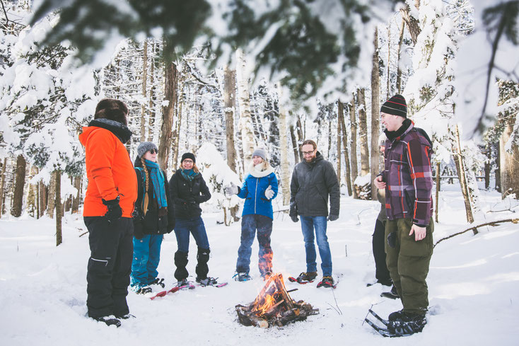 Équipe de travail en raquettes en forêt au bord d'un feu pendant l'hiver québécois durant une journée de consolidation d'équipe dans les cantons de l'Est pour Évasions Canadiana par Marie Deschene photographe pour Pakolla