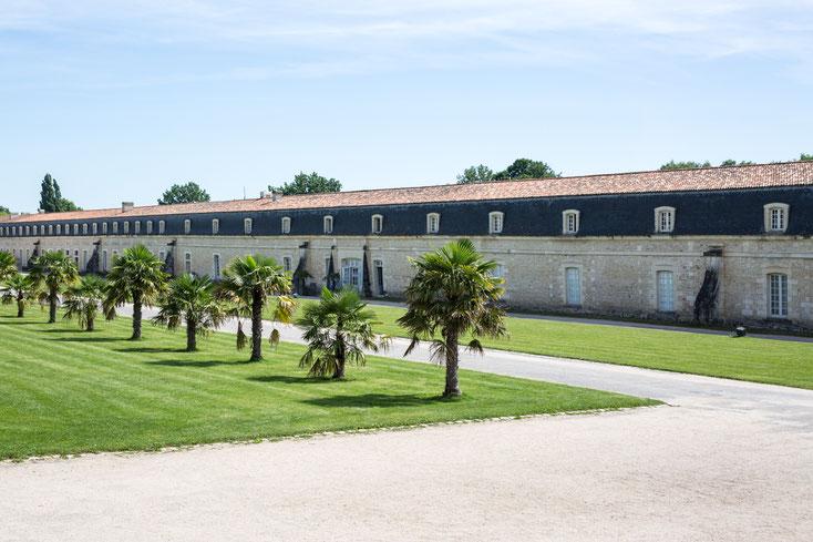 Bâtiment en long musée Corderie Royale Rochefort Sud-Ouest Charente-Maritime Région Nouvelle-Aquitaine France Europe photo extérieure avec palmiers en été par Marie Deschene photographe Pakolla