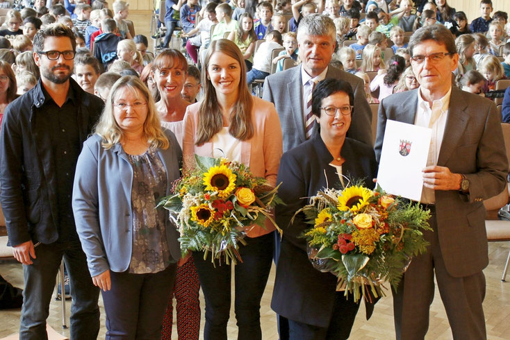 Der Vertreter der ADD, Horst Rauen (rechts), Bürgermeister Klaus Müller als Schulträger (2. v. rechts) sowie der ÖPR gratulierten Maria Dehen-Rummel (vorne rechts) sowie Kathrin Kriening (Mitte) im Beisein der Kinder und weiterer Ehrengäste.