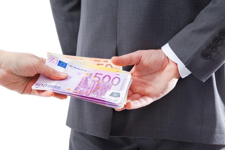 Ein Mann im Anzug nimmt hinter dem Rücken Bestechungsgeld an; Kurtz Detektei Hannover
