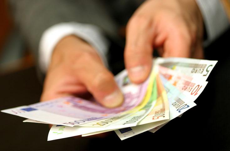 Mehrere Scheine Bargeld in der Hand eines Geschäftsmanns. Privatdetektive Hannover.