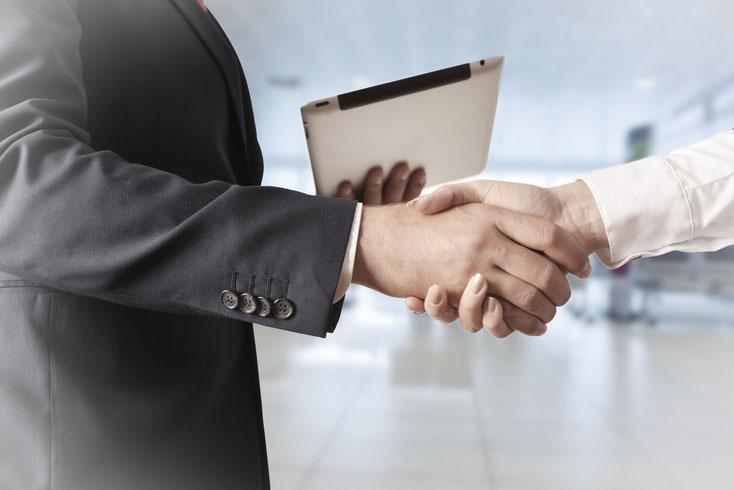 Zwei Geschäftsleute schütteln sich in klinischer Umgebung die Hand; Kurtz Detektei Hannover.