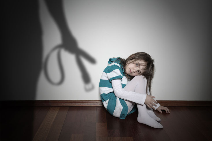 Mädchen sitzt mit angezogenen Knien auf dem Fußboden und guckt traurig. An der Wand der Schatten eines Mannes mit Gürtel in der Hand; Gewalt gegen Kinder, Kurtz Detektei Hannover