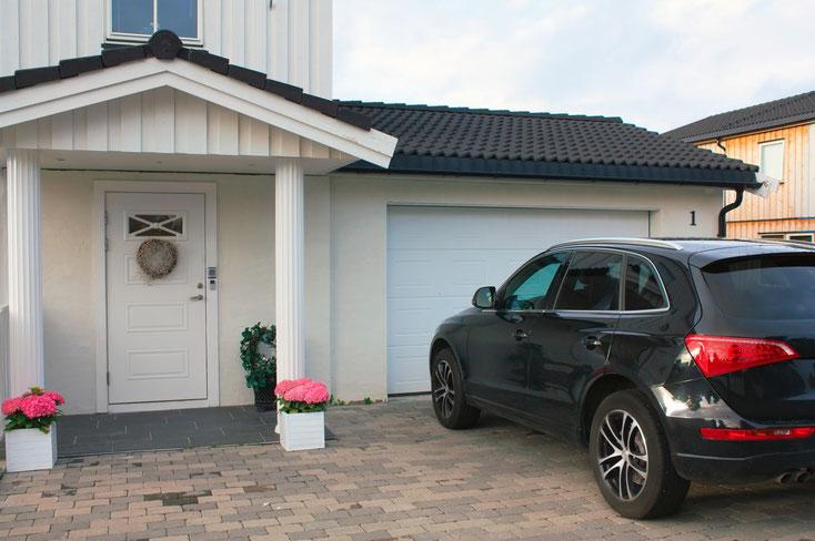 Ein schwarzer Audi SUV parkt vor einem Garagentor eines gehobenen Mittelstandshauses; Kurtz Detektei Hannover