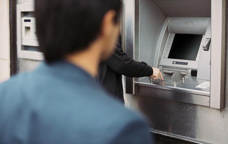 Ein Mann beobachtet einen anderen bei der Eingabe der PIN am Geldautomaten. Kurtz Detektei Hannover.