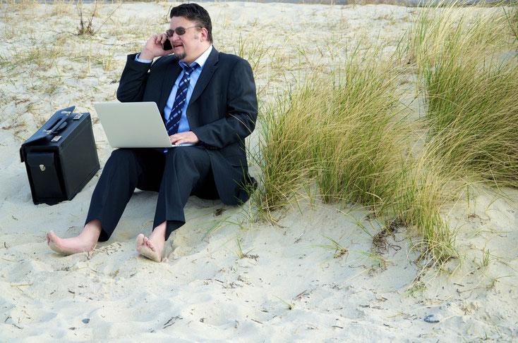Dicklicher Geschäftsmann sitzt im Anzug am Strand, Aktentasche neben sich, Laptop auf den Beinen und das Handy am Ohr; Kurtz Detektei Hannover