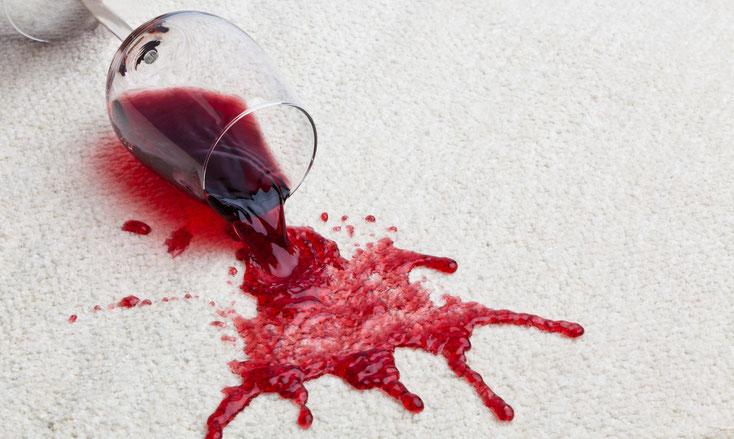 Umgestürztes Rotweinglas auf einem weißen Teppich; Kurtz Detektei Hannover