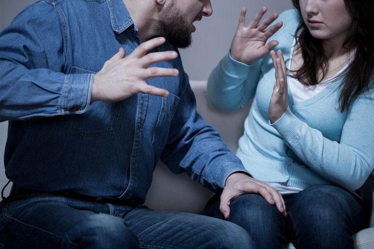 Mann bedroht Frau auf Sofa, Frau in Abwehrhaltung; Privatdetektive der Kurtz Detektei Hannover