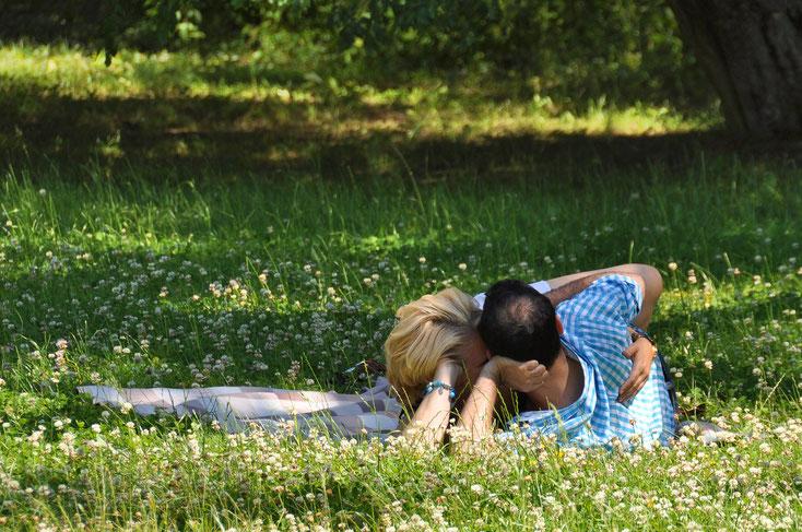 Ein Mann und eine Frau, beide mittleren Alters, umarmen sich liegend auf einer Wiese. Untreue in der Partnerschaft, Kurtz Detektei Hannover.