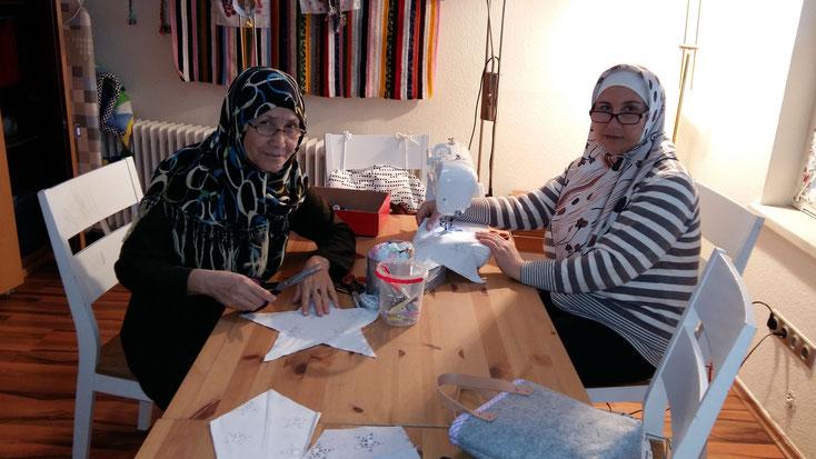 Hawa aus Afghanistan (links) und Rajaa aus Syrien nähen gemeinsam für den Basar am 1. Dezember. Bei der Arbeit verständigen sie sich auf Deutsch - und wenn das nicht klappt, mit Gesten.