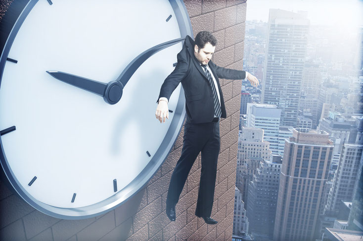 Geschäftsmann hängt an Uhr; Detektei Bonn, Detektiv Bonn, Wirtschaftsdetektei Bonn