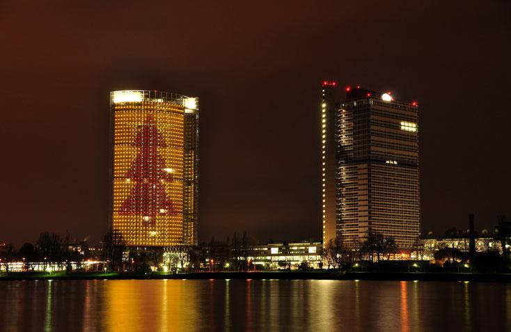UN-Campus und Post Tower mit Tannenbaum-Beleuchtung bei Nacht mit Blick über den Rhein; Kurtz Detektei Bonn.