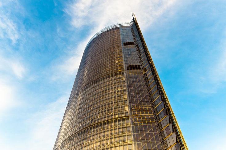 Der gelb leuchtende Post Tower in Bonn bei klarem Himmel; Kurtz Detektei Bonn