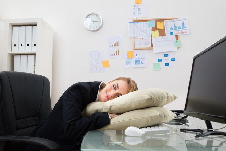 Frau schläft am Arbeitsplatz auf zwei Kopfkissen; Kurtz Detektei Bonn
