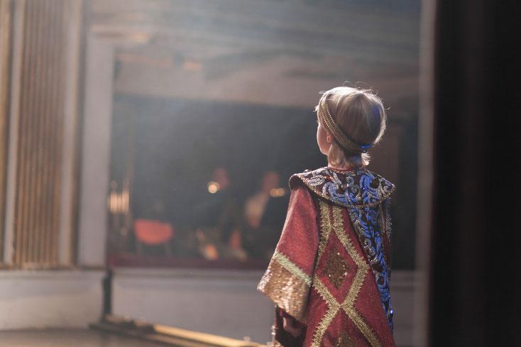 Ein Kind in mittelalterlicher Kostümierung auf einer Theaterbühne; Kurtz Detektei Bonn