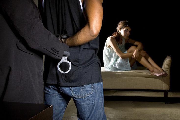 Frau sitzt mit angezogenen Beinen auf einem Sofa, während ihr Mann festgenommen wird; Kurtz Privatdetektei Bonn