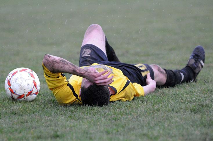 Ein Fußballspieler liegt mit Schmerzen auf dem Rasen; Detektiv Bochum | Kurtz Detektei Bochum