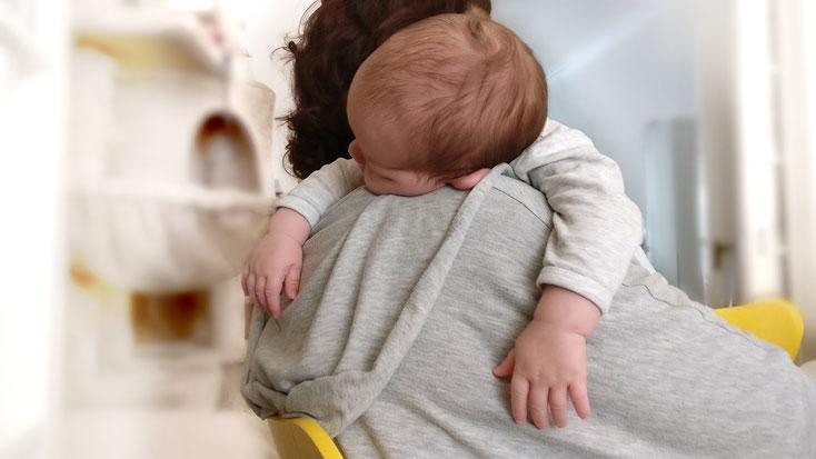 Säugling schlafend auf der Schulter seiner Mutter.