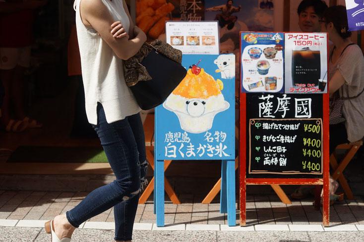 店先の路上に置かれた「鹿児島名物 白くまかき氷」の青い看板。白くまの絵と白くまの顔をしたかき氷が描かれている