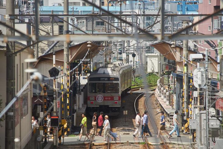 戸越銀座駅に停まる7700系の電車と踏切を渡る人たち