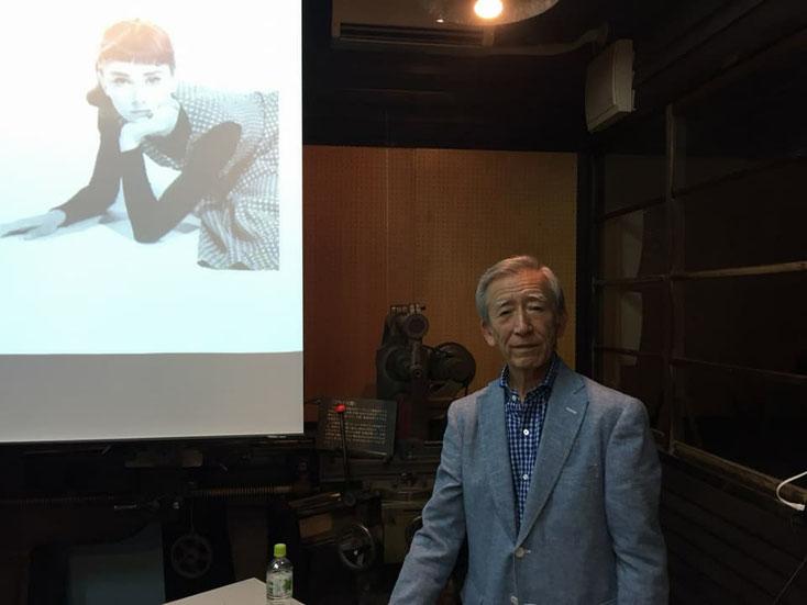 女優が映し出されたスクリーンを背景にした、岡茂光さん