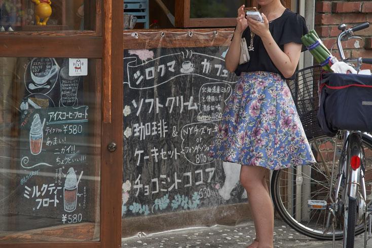 今風のお洒落なCafeの前で、花柄のスカートをはいた女性がスマホをいじっている