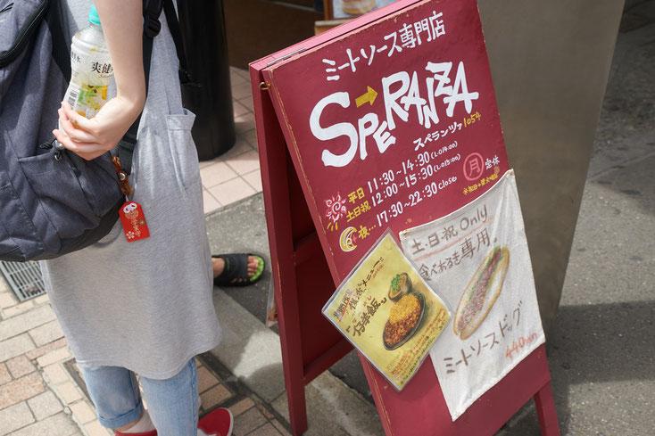 ミートソース専門店スペランツァの置き看板。布に描かれた食べ歩き専用ミートソースドックが貼られている。