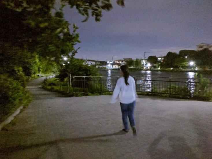 池の遊歩道を走っていく白い服、ジーンズの髪の長い女性サダコさん