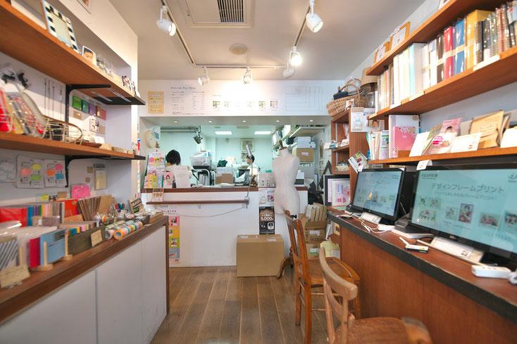 フォトカノンの店内。白い壁に明るい雰囲気。左側に商品(小物)が陳列されている。右側には客が座って作業できるカウンター。突き当り奥のカウンターの向こう側でスタッフが作業をしている。