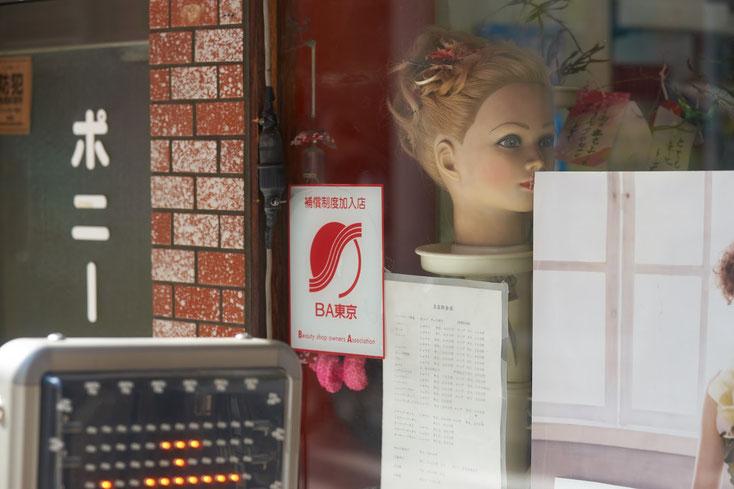 美容サロン「ボニー」の窓。店内にはマネキンヘッドが置かれている。