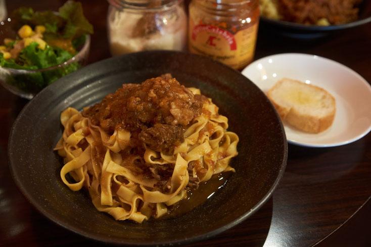 黒い皿に、美味しそうに盛り付けられた、ミートソーススパゲティ。麺は幅広な麺。