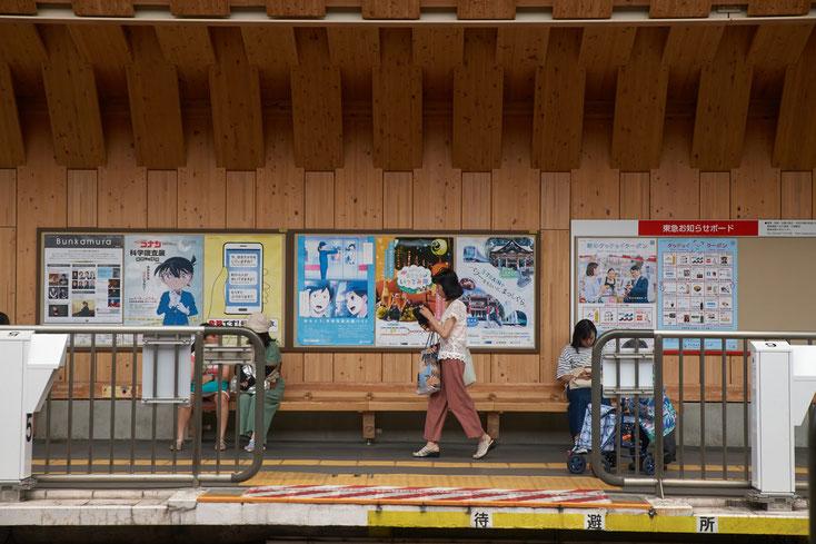 戸越銀座木造駅舎のホームを歩く人、電車を待つ人たち