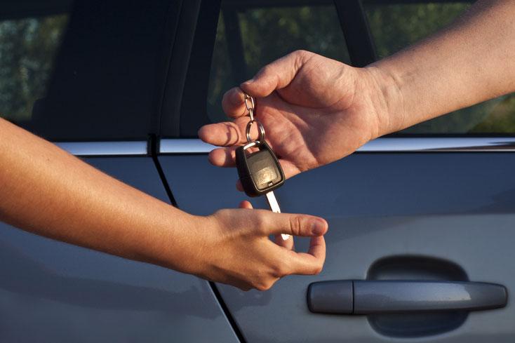 Zwei Männerunterarme: Der eine übergibt dem anderen einen alten Autoschlüssel, dahinter ein Fahrzeug. Kurtz Detektei Nürnberg.