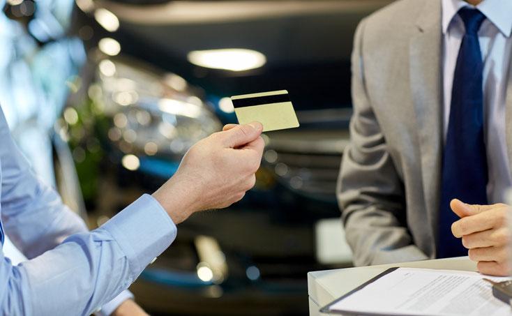 Zwei Männer sitzen über einem Vertrag in einem Autohaus, der Interessent hält dem Verkäufer eine Kreditkarte hin; Kurtz Wirtschaftsdetektei Nürnberg.