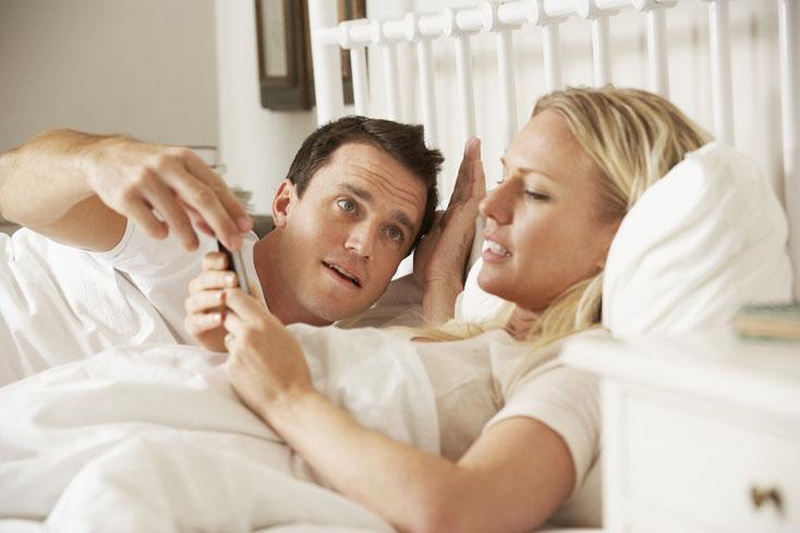 Mann streitet im Bett mit Frau, die ihr Handy bedient; Fremdgehen Kurtz Detektei Nürnberg