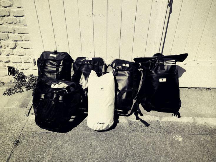Schwarz-weiß Aufnahme mehrerer Red Loon Taschen vor einer weißen Garage. Neben dem Kurierrucksack ganz rechts sind Satteltaschen und ein weißer Seesack von Red Loon zu sehen.