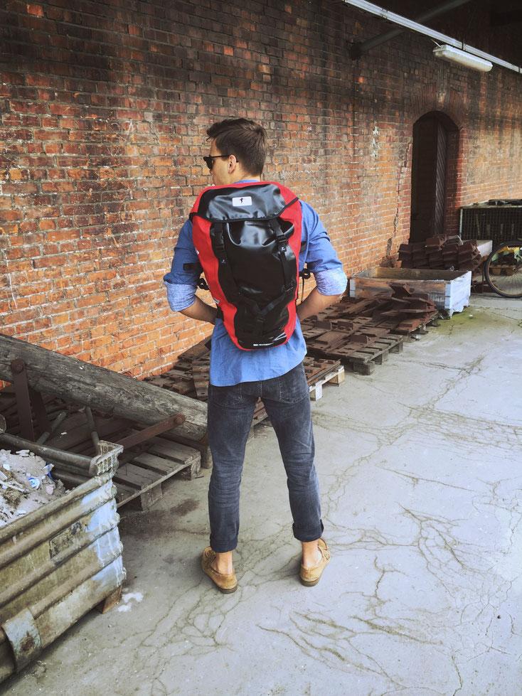 Mann trägt Red Loon Rucksack in schwarz-rot. Er trägt ein Jeanshemd und steht mit dem Rücken zum Betrachter. Im Hintergrund ist eine Backsteinmauer eines Gebäudes und einige verrostete Metallteile auf alten Paletten zu sehen.