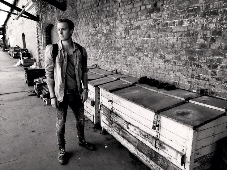 Schwarz-Weiß Aufnahme eines Mannes, der zerrissene Jeans trägt und vor einem industriellen Gebäude steht. Auf dem Rücken trägt er einen Rucksack von Red Loon.
