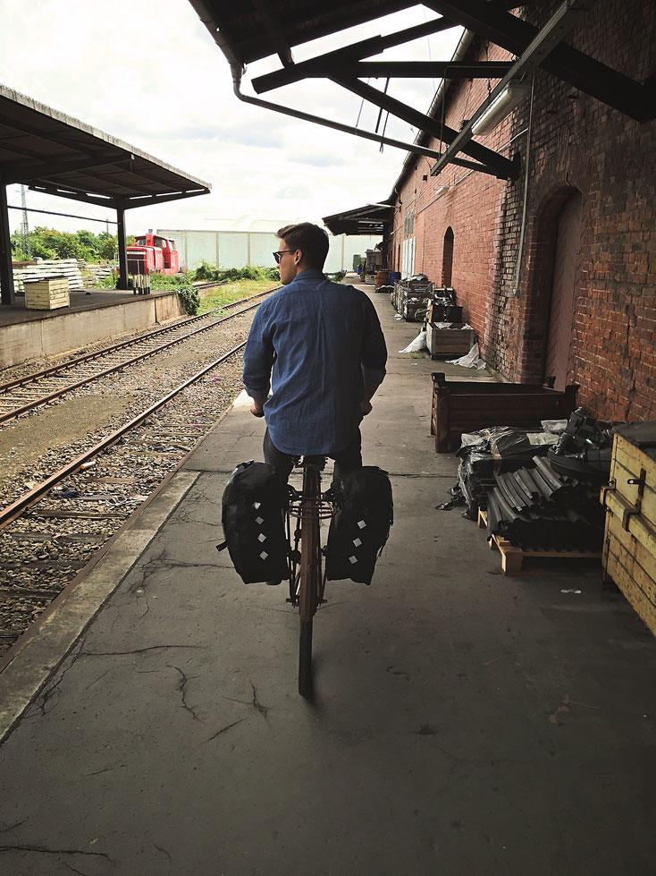 Mann, der auf seinem verrosteten Fahrrad an alten Bahngleisen entlangfährt. Er fährt vor dem Betrachter weg und hat seinen Blick nach links in Richtung der Gleise gerichtet.