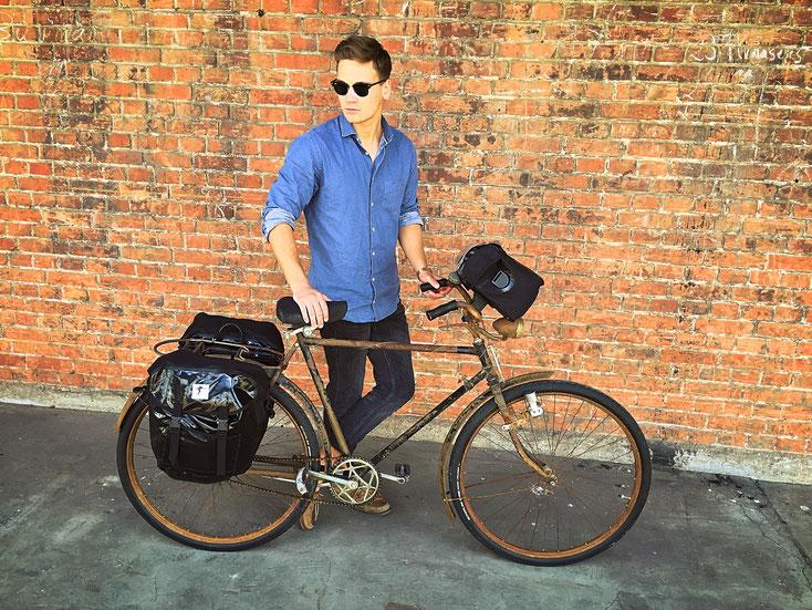 Mann steht mit seinem alten Rad vor einerBacksteinmauer, den Blick leicht nach links unten gerichtet. An den Gepäckträger des Rades sind zwei schwarze, glänzende Red Loon Satteltaschen befestigt. Am Lenker ist eine schwarze Red Loon Lenkertasche zu sehen.