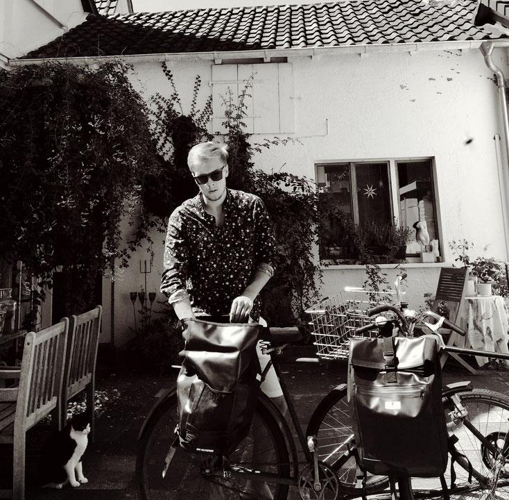 Schwarz-weiß Aufnahme: Mann mit Sonnenbrille steht in einem Hof vor einem weißen Haus, das leicht mit Pflanzen bewachsen ist. Er packt etwas in seine Red Loon Satteltasche, die am Gepäckträger des Rades befestigt ist.