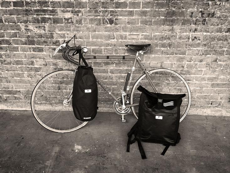 In schwarz-weiß ist ein Rennrad zu sehen, das an eine Backsteinmauer gelehnt ist. Am Lenker hängt ein schwarzer Red Loon Seesack und vor dem Hinterrad steht ein schwarzer Red Loon Kurierrucksack.