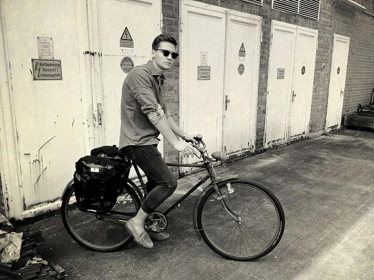 In schwarz-weiß ist ein junger Mann mit Sonnenbrille auf einem alten Herrenrad mit zwei schwarzen Satteltaschen zu sehen.