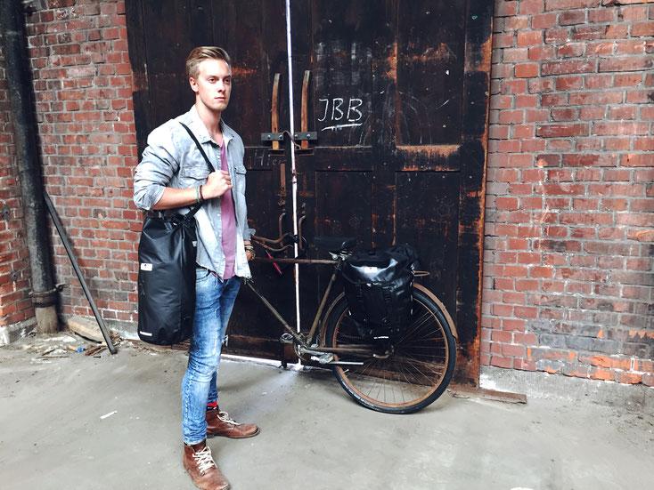 Mann steht vor einem dunklen, abgenutzten Holttor, an das ein altes Fahrrad mit Red Loon Satteltaschen gelehnt ist. Er trägt einen schwarzen Red Loon Seesack über der Schulter.