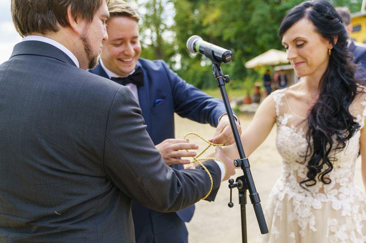 Da die beiden grosse Irland Fans sind, wurden keine Ringe getauscht sondern der keltische Brauch 'tying the knot' vollzogen. Hierbei wird der symbolische 'Bund fürs Leben' mit einem Band und Knoten um die Handgelenke des Brautpaares besiegelt.