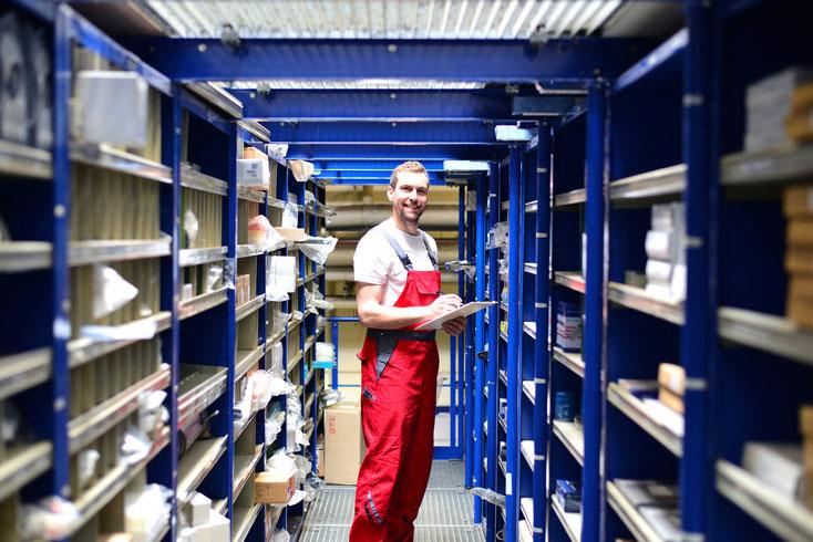 Ein Arbeiter prüft den Warenbestand im Lager und lächelt in die Kamera. Kurtz Wirtschaftsdetektei Stuttgart